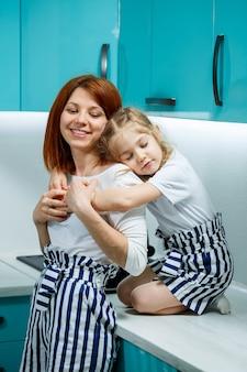 Maman et sa fille dans la cuisine cuisinent, mangent, s'embrassent. le concept d'une famille heureuse. relations parents-enfants, enfance joyeuse