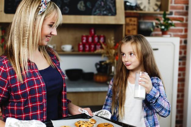 Maman et sa fille dans une cuisine goûtent ensemble des biscuits au chocolat frais et au lait avec du lait