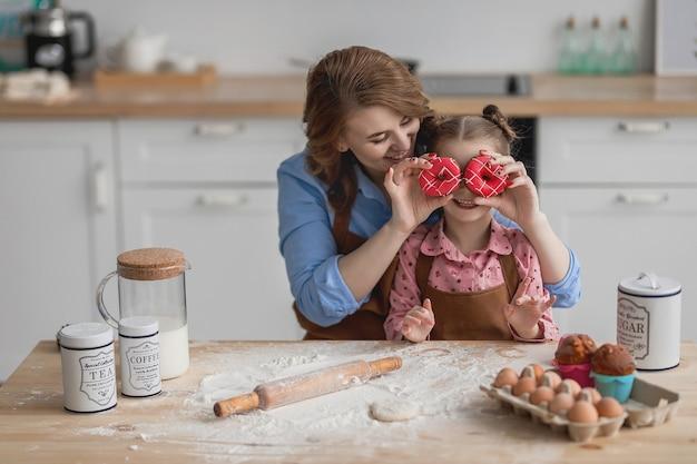 Maman et sa fille dans la cuisine à la table de la cuisine font des grimaces avec un beignet