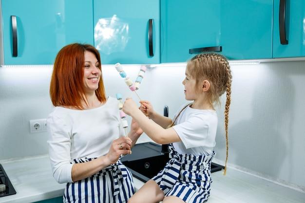 Maman et sa fille dans la cuisine turquoise jouent avec des guimauves. belles relations familiales. notion de famille heureuse