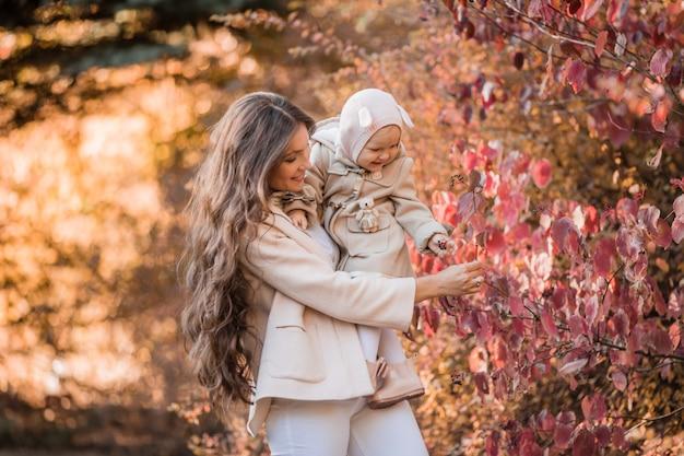 Maman et sa fille dans le parc en automne pour une promenade