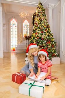 Maman et sa fille écrivent une lettre au père noël. mise au point sélective.