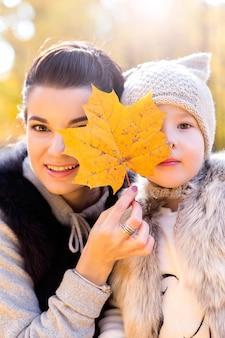Maman et sa fille ferment les yeux avec des feuilles d'automne