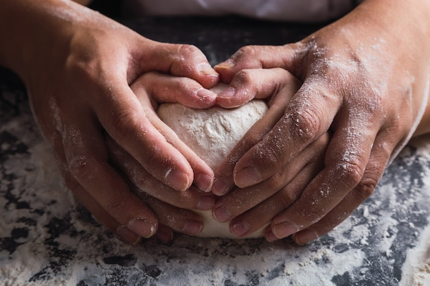 Maman et sa fille font un cœur avec leurs mains en préparant la pâte.