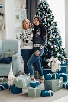 Une maman et sa fille heureuses déballent les cadeaux de noël