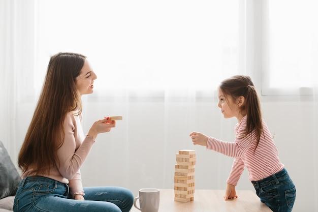 Maman et sa fille jouent à un jeu de société dans le salon.