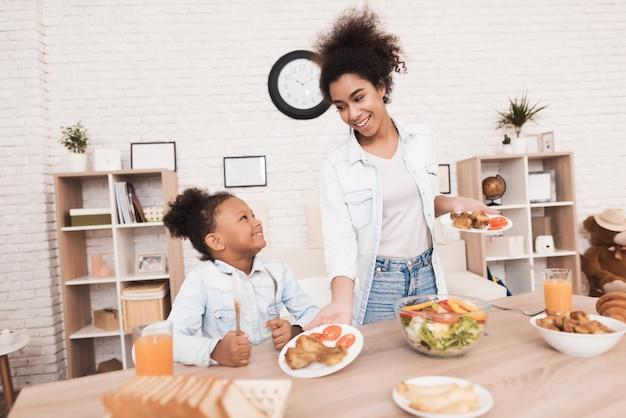 Maman et sa fille mangent ensemble dans la cuisine.