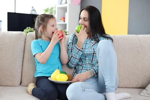 Maman et sa fille mangent des fruits assises sur un canapé