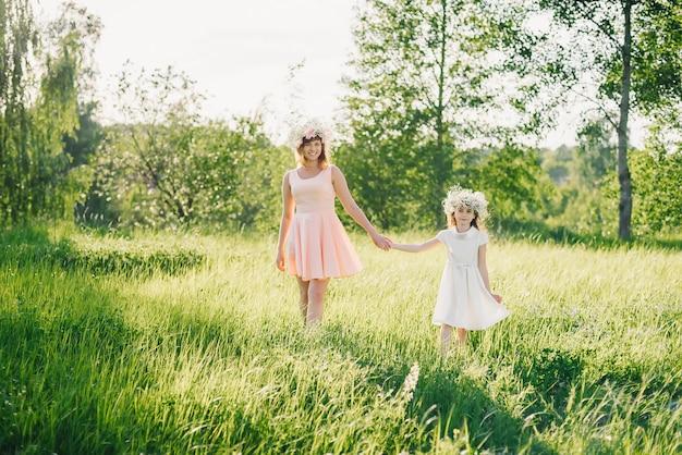 Maman et sa fille marchant sur le terrain en été journée ensoleillée au coucher du soleil
