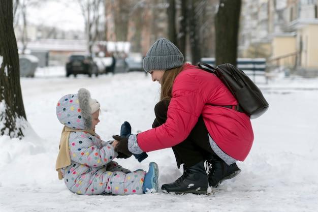 Maman et sa fille marchent dehors en hiver et profitent de la première neige.