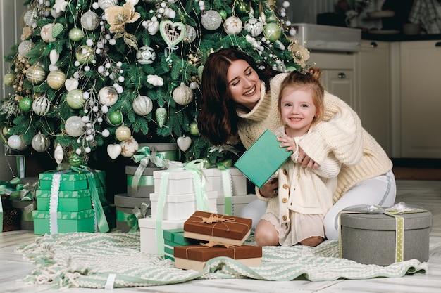 Maman et sa fille ouvrent des cadeaux de noël