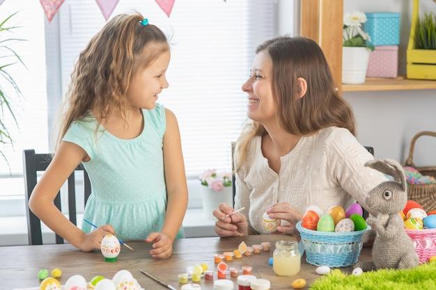 Maman et sa fille peignent des œufs pour les vacances lumineuses de pâques. asseyez-vous pour être heureux avec les peintures