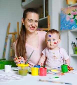 Maman et sa fille peignent sur une toile à l'école de dessin.