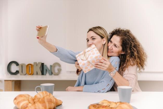 Maman et sa fille posant pour selfie avec présent