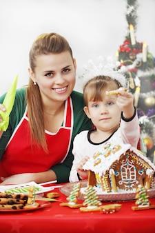Maman avec sa fille prépare une maison au gingembre