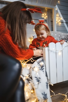 Maman avec sa fille en pulls chauds rouges saute sur le lit. bonne maternité. relations familiales chaleureuses. intérieur de noël et du nouvel an. amour. notion de famille.