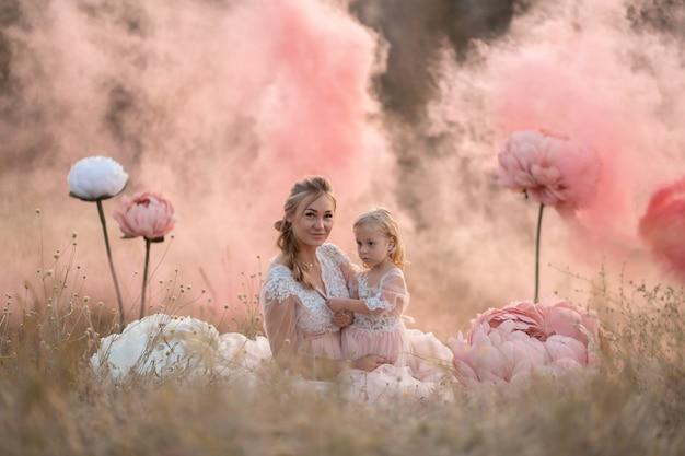 Maman et sa fille en robes de conte de fées roses sont assis dans un champ entouré de grandes fleurs décoratives roses
