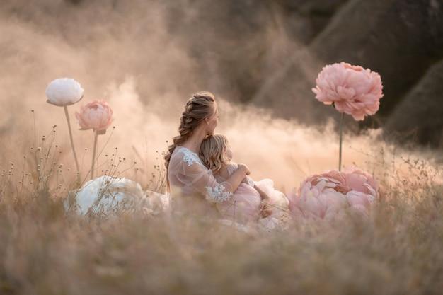 Maman et sa fille en robes fabuleuses roses regardent au loin, assises dans un champ entouré de grandes fleurs décoratives roses