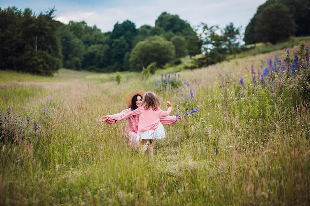 Maman et sa fille en robes roses courent pieds nus sur le terrain