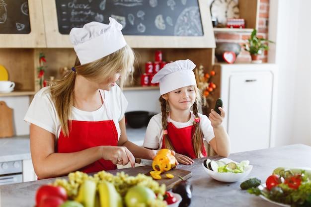 Maman et sa fille s'amusent dans la cuisine en préparant différents légumes pour un dîner
