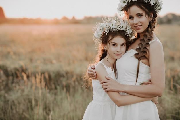 Maman et sa fille s'embrassant dans des robes blanches avec des tresses et des couronnes florales en été