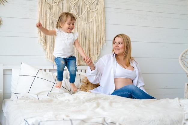Maman et sa fille sautent et s'amusent sur le lit dans la chambre