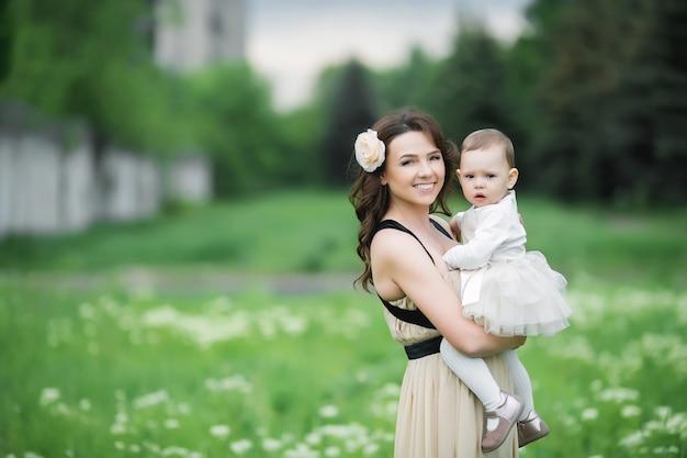 Maman et sa fille se promène au printemps sur un pré vert dans le village