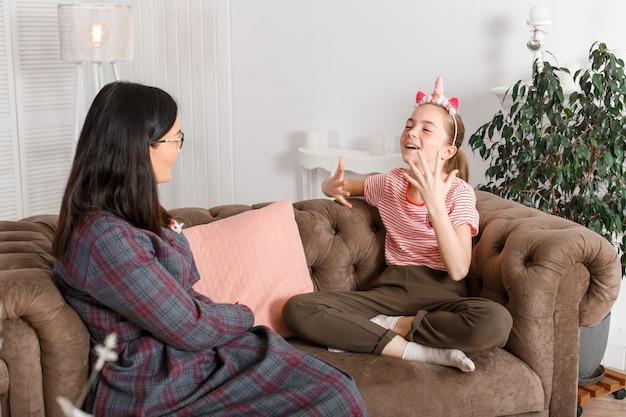 Maman et sa fille sont assises sur le canapé et discutent