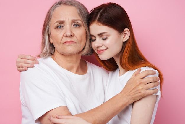 Maman et sa fille en t-shirts blancs s'embrassent l'amitié familiale. photo de haute qualité