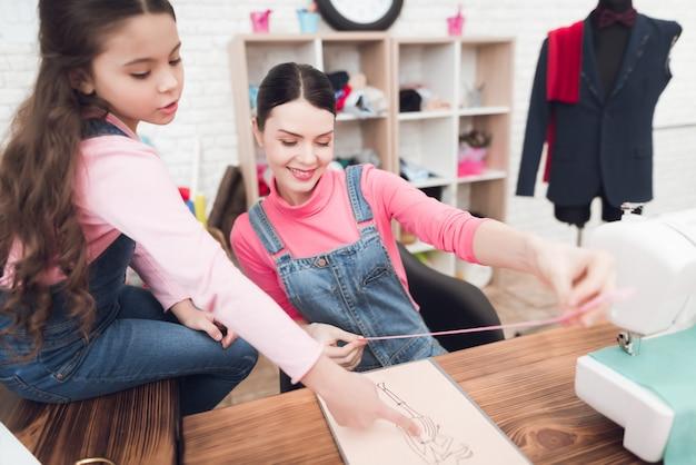 Maman et sa fille travaillent ensemble dans un atelier de couture