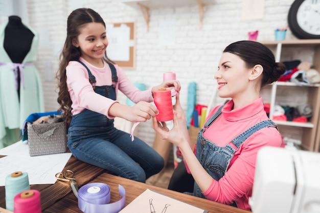 Maman et sa fille travaillent ensemble dans un atelier de couture.