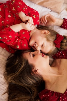 Maman et sa petite fille s'allongent sur le lit face à face, elles sont heureuses