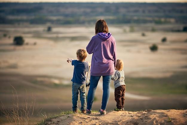 Maman se tient avec ses deux fils sur une colline au coucher du soleil