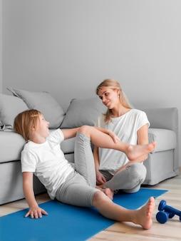 Maman avec séance d'entraînement fille sur tapis