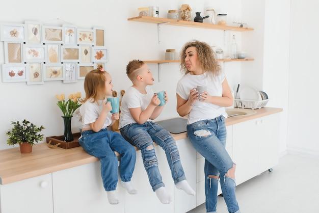 Maman avec ses deux enfants assis sur la table de la cuisine.