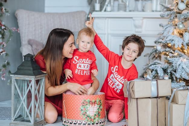 Maman et ses deux fils, vêtus de vêtements du nouvel an, passent du temps à l'arbre de noël, s'habillent, s'amusent