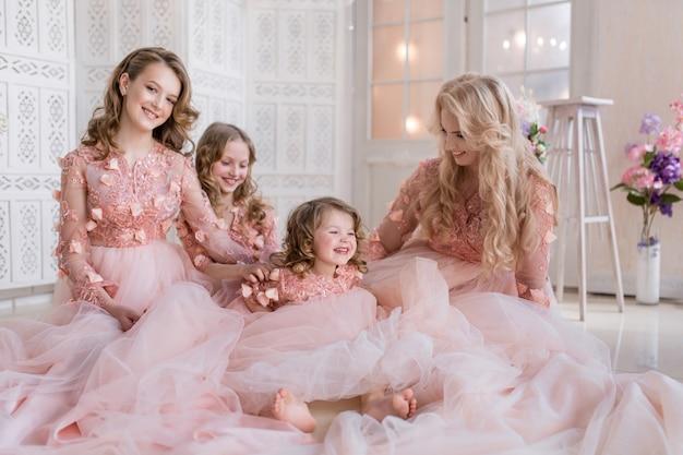 Maman et ses trois filles vêtues de gawns roses posent dans une chambre blanche de luxe