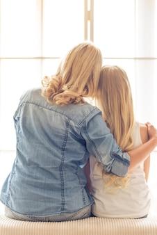 Maman de soin embrasse une petite fille à la maison.