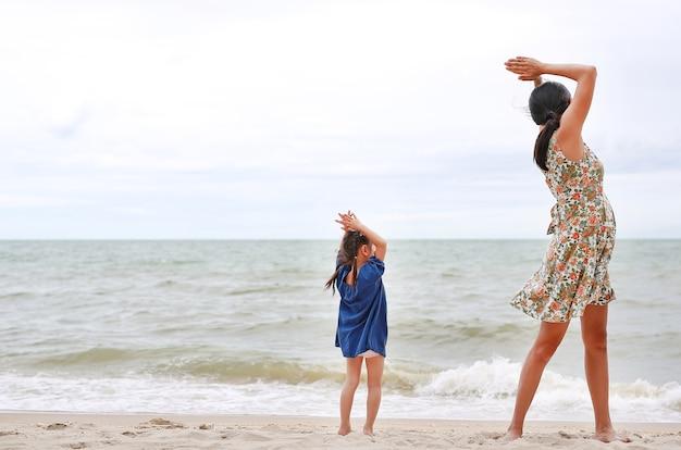 Maman et son enfant font des exercices de yoga à la plage