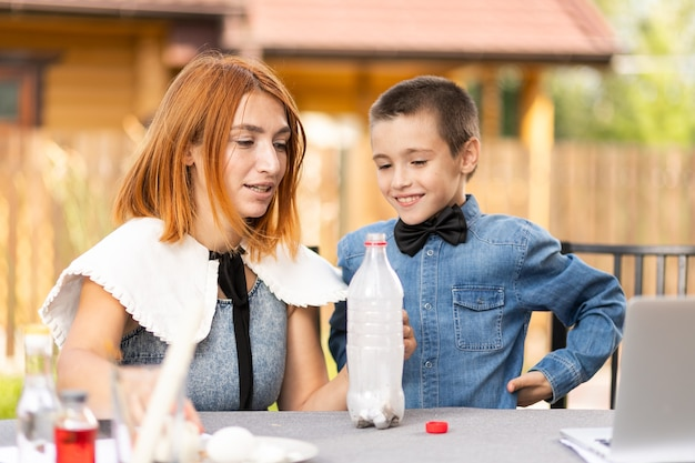 Maman et son fils font des expériences physiques à la maison. une expérience avec un enfant sur la façon de placer un œuf à la coque dans le goulot étroit d'une bouteille en plastique en utilisant le feu. créativité maison avec un enfant