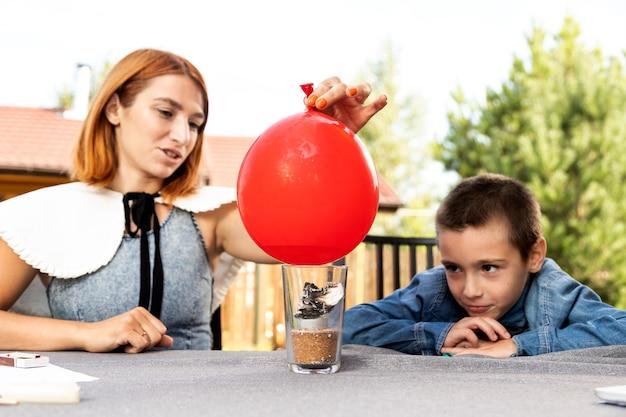 Maman et son fils font des expériences physiques à la maison. une expérience avec un enfant pour savoir laquelle des balles est vide ou avec de l'eau éclatera plus rapidement du feu. étape 4
