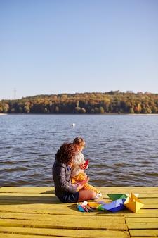 Maman et son fils jouant avec des bateaux en papier au bord du lac