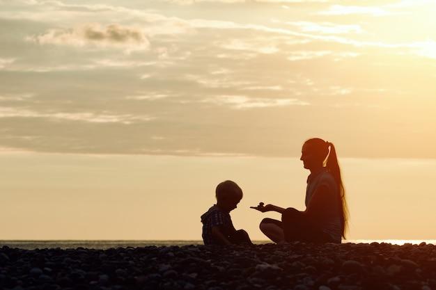 Maman et son fils jouant sur la plage avec des pierres