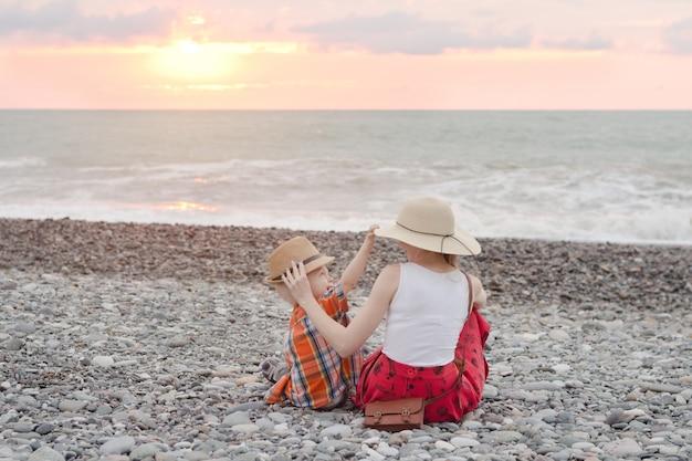 Maman et son fils jouent sur la plage de galets. heure du coucher du soleil. vue arrière