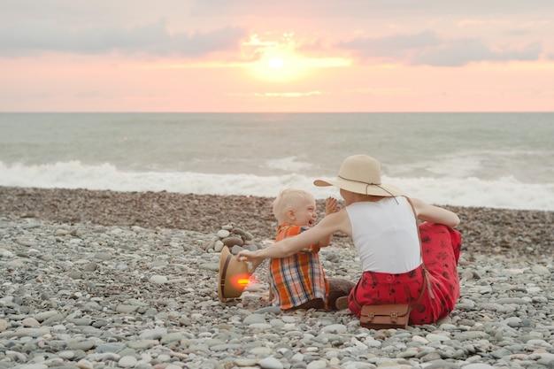 Maman et son fils jouent sur la plage de galets.