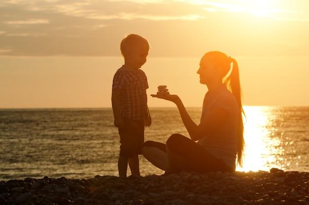 Maman et son fils jouent sur la plage avec des pierres