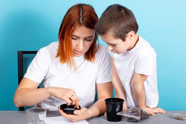 Maman et son fils mettent de la terre dans un pot noir pour planter une graine et faire pousser une plante d'intérieur sur la table sur un fond bleu.