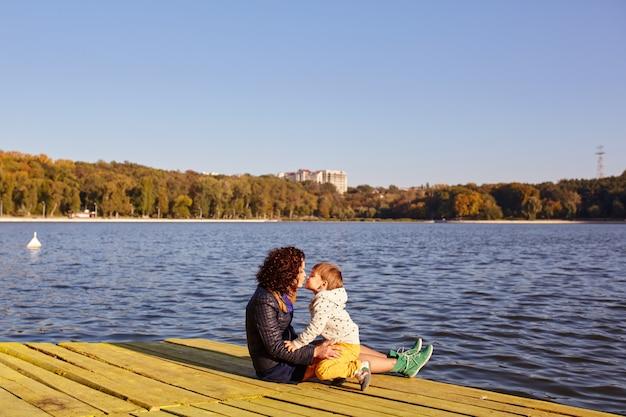 Maman et son fils se reposant au bord du lac