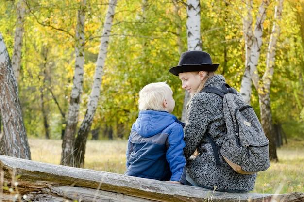 Maman et son fils sont assis dans la forêt d'automne sur une bûche. vue arrière