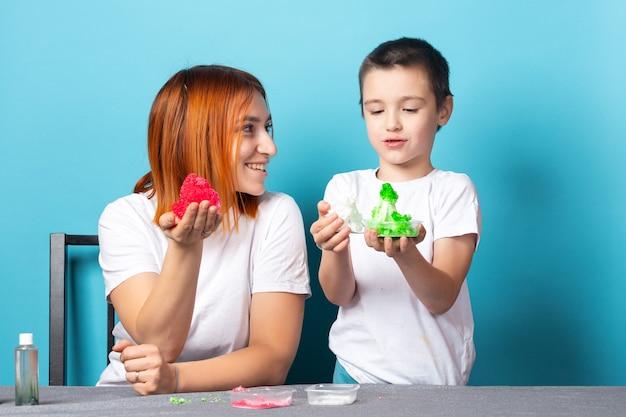 Maman et son fils tiennent des cristaux rouges et verts sur une surface bleue.